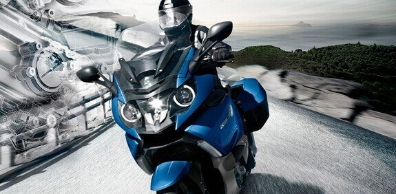 Blue touring motorcycle driving down a road
